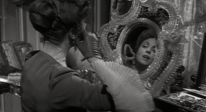 Madame de... (Danielle Darrieux) tries on her earrings.